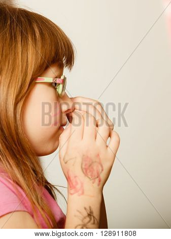 Childhood and development concept. Little girl schoolchild in glasses with the body painted face profile