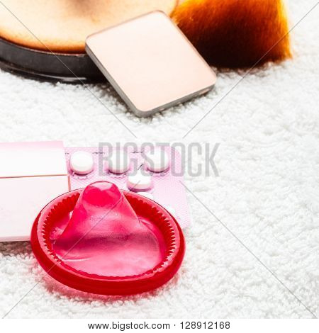 Healthcare medicine contraception and birth control. Closeup oral contraceptive pills condom and cosmetics.