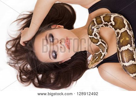 women with dark smoky eye's laying with snake. Fashion.  Isolated on white