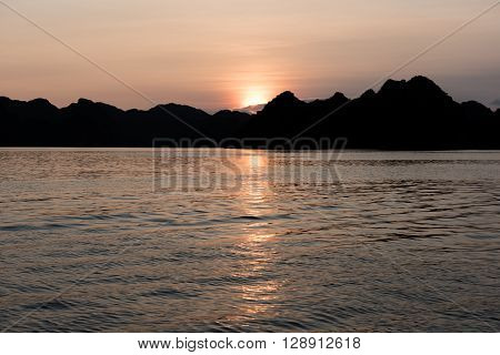 View of the large limestone karsts formation in Ha Long Bay, Vietnam during the sunset. During sunset, the sepia view is awesome and a pleasant treat to the eye of the tourists.