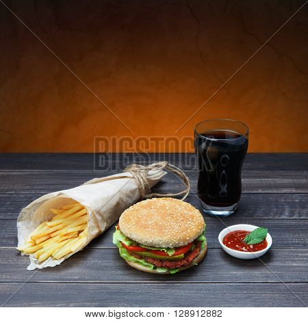 Fast food. Hamburger, potato fries, cola drink. Takeaway food. Wrapped French fries, packaging, Cola glass, tomato sauce, double cheese hamburger at rustic wood and brown background.
