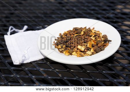Mulling spices on white plate place on wrought iron table with small white cloth spice bag underneath dish. Rustic horizontal image with copy space.