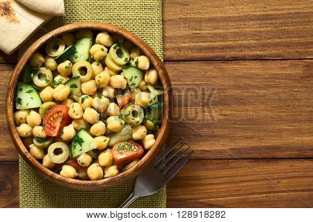 Chickpea salad with green olives cucumber cherry tomato and parsley served in wooden bowl pita bread pieces on the side photographed overhead with natural light