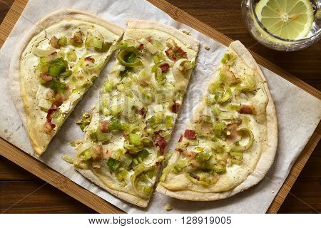 Homemade leek and bacon tarte flambee a traditional French and German oven baked pizza-like pie photographed overhead with natural light