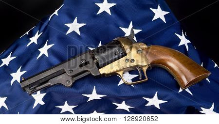 Old west six shooter gun on American flag.