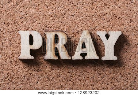 Wooden pray text is on the corkboard background.
