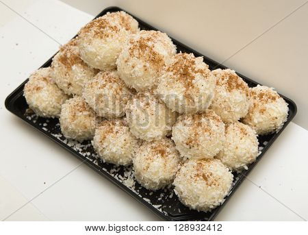 Sweet balls strewed by a coconut shaving and ground coffee