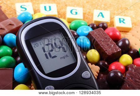 Glucose meter with word sugar heap of candies cookies and brown cane sugar unhealthy food concept of diabetes and reduction of eating sweets