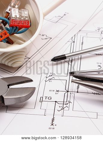 Metal pliers screwdriver and cable connections in electrical box on electrical construction drawing work tool and drawing for engineer jobs concept of building house
