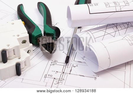 Metal pliers screwdriver electric fuse and rolls of diagrams on construction drawing of house work tool and drawing for projects engineer jobs concept of building house