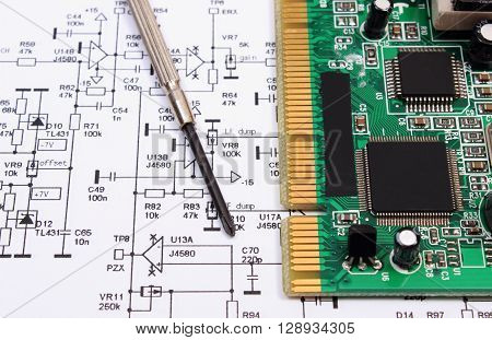 Printed circuit board with electrical components and precision screwdriver lying on construction drawing of electronics drawings and precision tools for engineer jobs