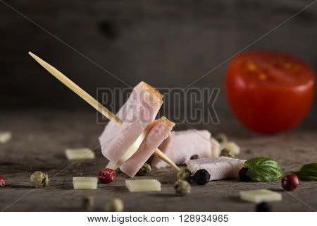 Mini ham and cheese appetizer with spices over wooden background