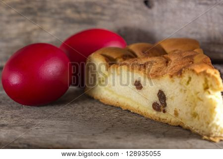 Romanian cake Pasca with cheese and traditional colored easter egg wood background