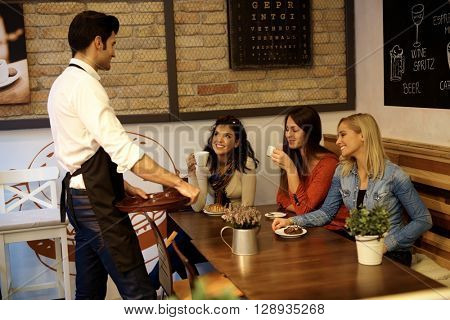 Male waiter chatting with pretty young girls in cafeteria, smiling.