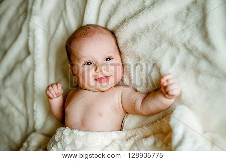 baby in a knitted cap is covered with a blanket and smiling