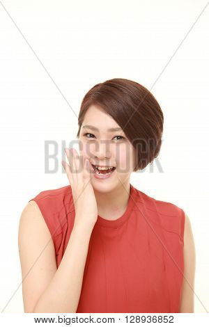 young Japanese woman pleased on white background