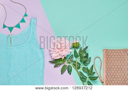 Summer Fashion Ladies clothes accessories set. Glamor lace dress,  stylish handbag clutch, necklace, pink flowers. Unusual creative elegant look. Overhead, romantic outfit. Top view, blue background