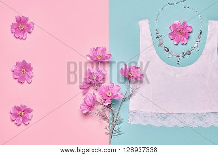 Fashion woman clothes accessories set. Glamor lace top, stylish necklace and summer pink flowers. Elegant trendy date outfit. Unusual creative girl. Overhead, romantic.Top view, blue pastel background