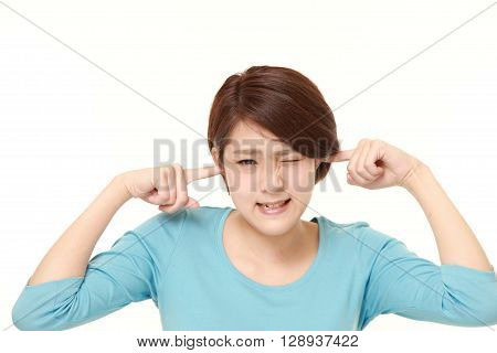 Young Japanese woman suffers from noise on white background