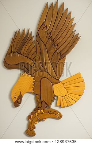 flying posed intarsia two tone wooden eagle with fish in claws