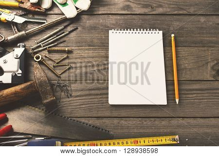 old tools with a notebook with blank pages on wooden table in the workshop top view