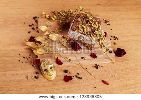 Beautiful creative still life. Golden twigs box and theatrical mask.