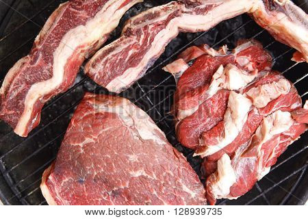 traditional south america cuisine : raw beef asado ribs, big fillet, steak on big classic round barbecue grill isolated on white background