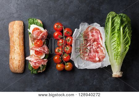 Ciabatta sandwich with romaine salad, prosciutto and mozzarella cheese over stone background. Top view