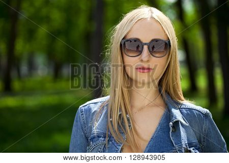 Beautiful blonde woman in sunglasses. Calm blond in blue jeans jacket on summer green park background