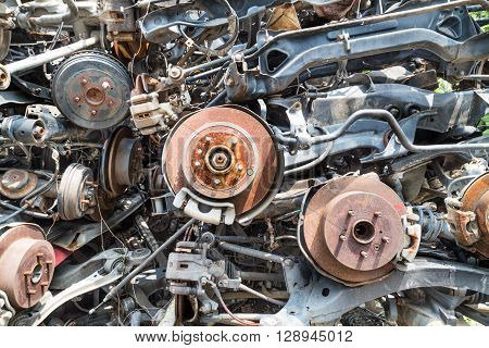 Closeup on heaps of used old auto disk and drum brake parts for recycling at workshop