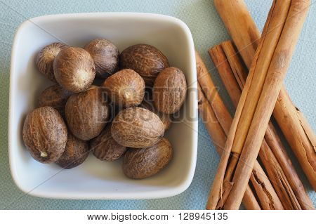 Whole Nutmegs in a small ceramic bowl with Cinnamon sticks.