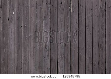 fence of vertical old brown purple planks or side of farm shed