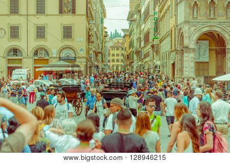 FLORENCE, ITALY - JUNE 12, 2015: Various people walking around a square in Florence, tree carts at the end as attraction, heads only. Unidentified tourists