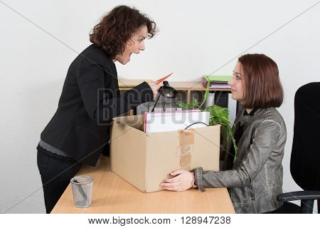 Woman Shouting Against Female Employee With Box