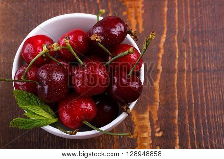 Red ripe cherries in a white bowl on rustic wooden background
