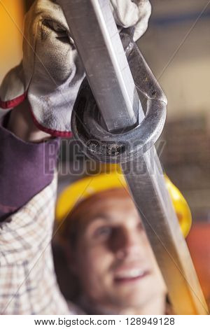 Young Metalworker Hooks A Steel Tube To Lift