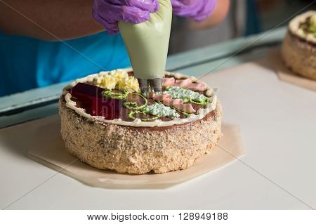 Colorful cake with ornament. Cake being decorated by worker. How confectionery is made. It's a dream job. ** Note: Shallow depth of field
