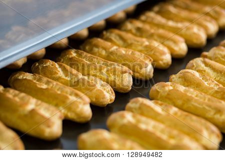 Rows of yellow eclair shells. Conveyor belt with eclairs. Crispy dough of high quality. New cycle of production.