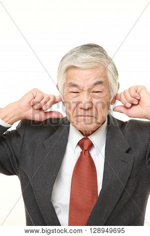 portrait of senior Japanese businessman suffers from noise