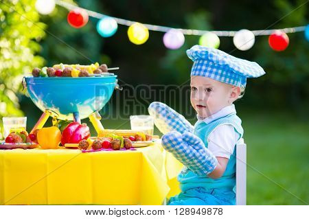 Children grilling meat. Family camping and enjoying BBQ. Little boy at barbecue preparing steaks kebab and corn. Kids eating grill and healthy vegetable meal outdoors. Garden party for toddler child