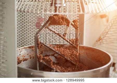 Industrial mixer with brown dough. Huge industrial mixer blade. Ingredient for chocolate sweets. First stage of production.