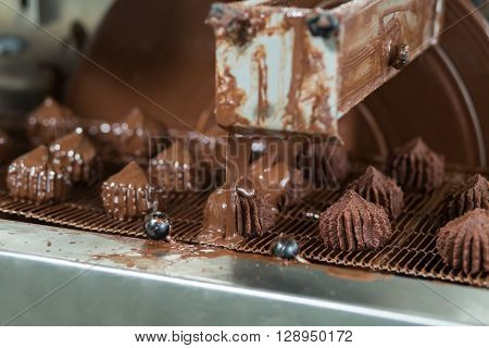 Conveyor pouring liquid onto sweets. Dark candies on conveyor line. Dessert produced at local plant. Chocolate glaze for tasty candies.