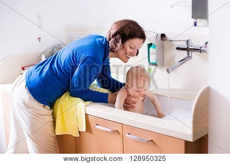 Mother washing her baby in a hospital room. Mom bathing little boy during clinic stay at children station. Health care and for young kids. Parent and child stay in room. Infant recovery after sickness