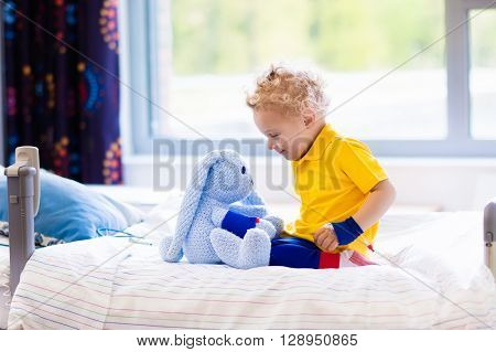 Little boy playing with his toy in bed in hospital room. Child with IV tube and pulse oximeter in modern clinic. Kid recovering from sickness. Post operative care at children station. Kids health care