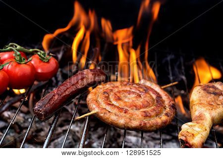Grill concept.  roll sausage and tomatoes on grill with flare on backgroun