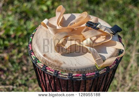 Djembe drum at green grass background. Closeup.