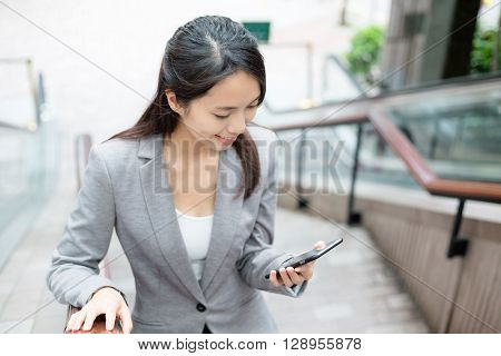 Business woman walking up stairs and look at cellphone