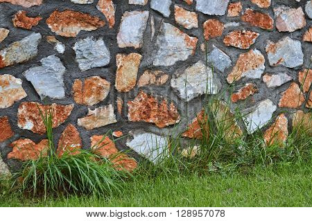 Detail of stonewall and green grass for background