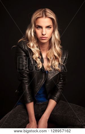 portrait of a fashion biker woman in leather jacket sitting in studio