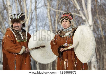 KAMCHATKA RUSSIA - FEB 5 2012: Man and woman in the Koryak national dress stand with tambourines in the background of a winter forest. Concert Koryak National Folklore Dance Group. Eurasia Russian Far East Kamchatka Region.